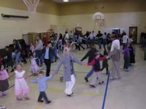 photograph of children and parents dancing together at an old-time traditional dance