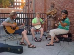 photo of old-time musicians playing guitar, banjo, and fiddle outside at Ragtag