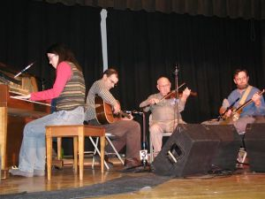 photo of old-time musicians playing piano, guitar, fiddle, and banjo